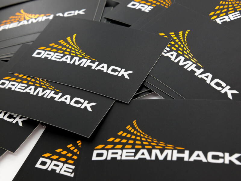 Bild på svarta visitkort för Dreamhack. Bakgrunden är svart och logotypen som är tryckt på kortet är i orange folie.
