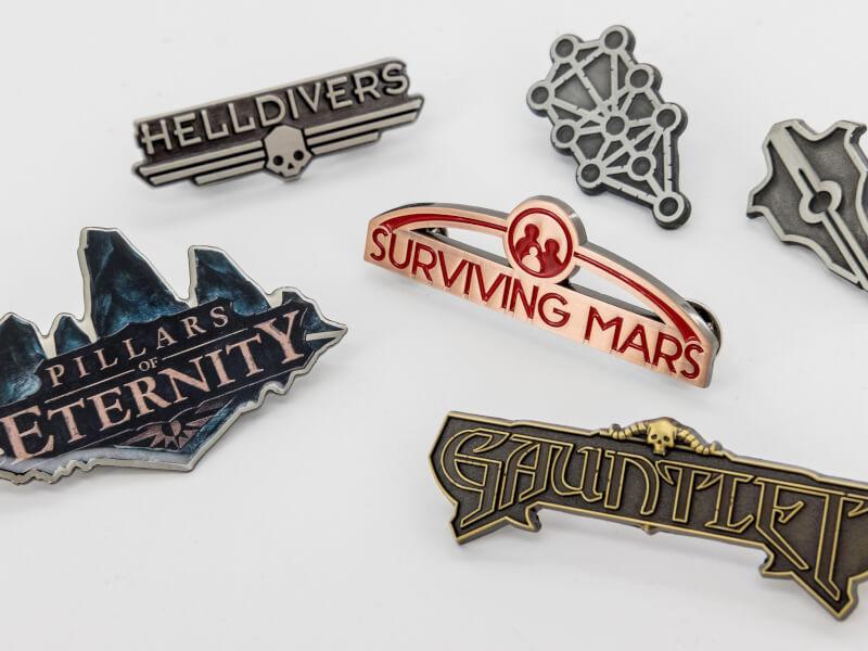 Bild på pins gjutna i metall. Bilden visar flera olika logos för datorspel